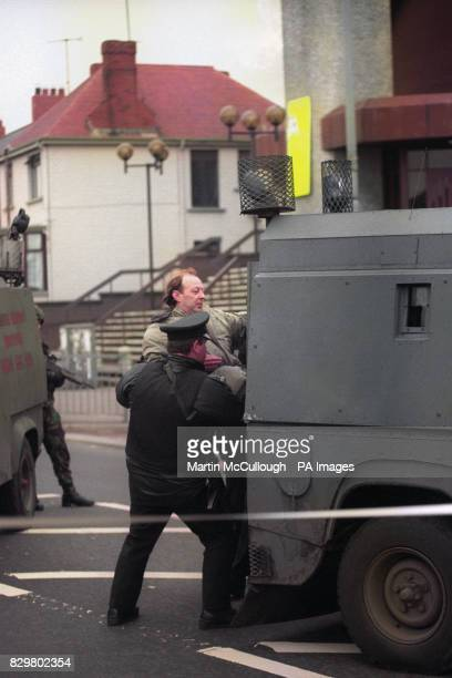 Sinn Fein Councillor Joe Austin is forcefully removed from the scene of a Loyalist RPG attack on Sinn Fein headquarters in Belfast's Andersonstown