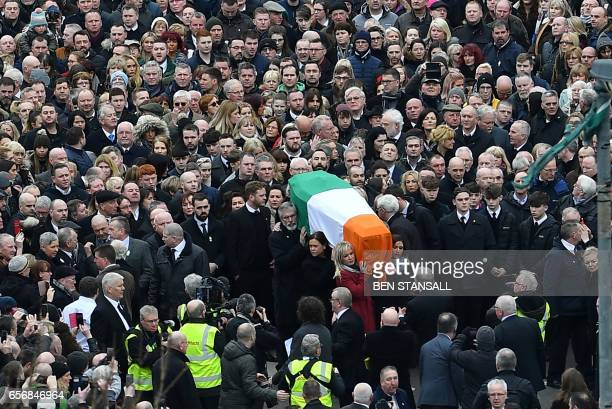 TOPSHOT Sinn Fein President Gerry Adams and Sinn Fein Northern Ireland Leader Michelle O'Neill take the part of pallbearers in the funeral procession...