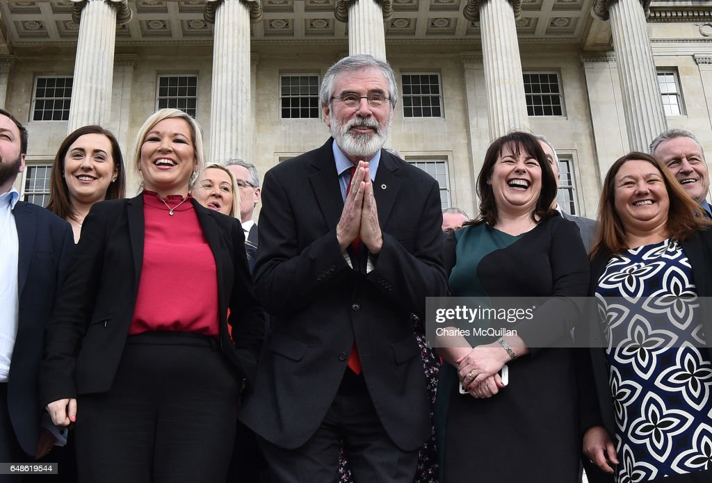 Sinn Fein president Gerry Adams (C) bows to a group of Japanese tourists as he attends a press call alongside northern leader Michelle O'Neill (3rd L) at Stormont on March 6, 2017 in Belfast, Northern Ireland. Elected MLA's return today after last weeks elections with the two largest parties, Sinn Fein and the Democratic Unionist party commencing talks to form a new power sharing executive government. Sinn Fein northern leader Michelle O'Neill has stated that there can be no agreement if former First Minister Arlene Foster of the DUP is nominated again for the position.