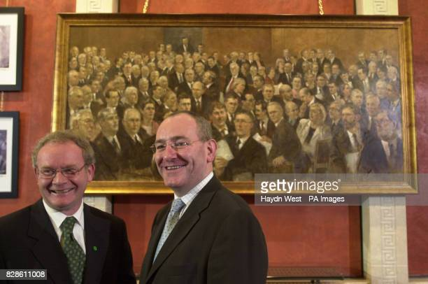 Sinn Fein's Martin McGuiness and SDLP leader Mark Durkan chat to journalists in front of a painting of the Northern Ireland Assembly in session which...