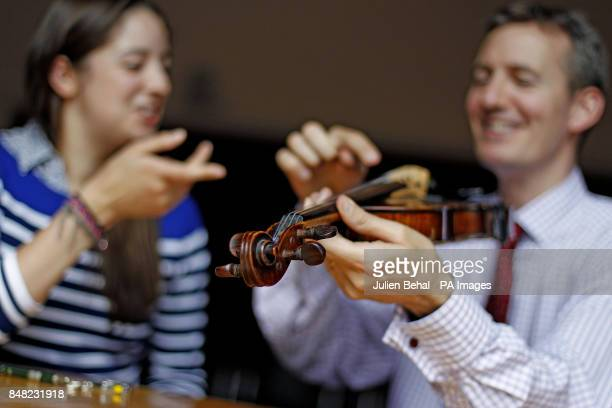 Siobhan Kelliher has her copy of a Stradivarius Violin examined byTim Ingles Head of Musical Instruments with Sotheby's in London during a free...