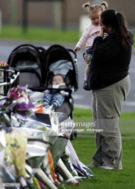 Siobhan Sloan and baby Lauren with baby Sean in his pram leaving flowers outside RAF Kinloss station in tribute to the 14 British service personnel...