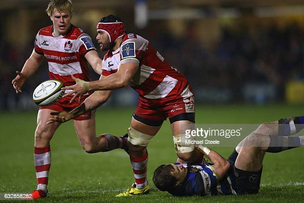 Sione Kalamafoni of Gloucester feeds a pass as Jack Wilson of Bath holds on in the tackle during the Anglo Welsh Cup match between Bath Rugby and...