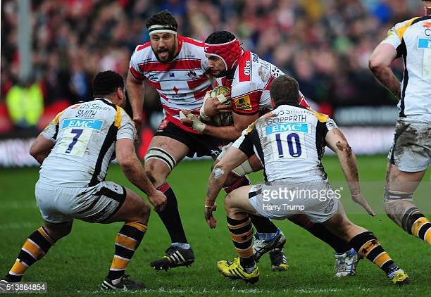 Sione Kalamafoni of Gloucester is tackled by George Smith of Wasps and Jimmy Gopperth of Wasps during the Aviva Premiership match between Gloucester...