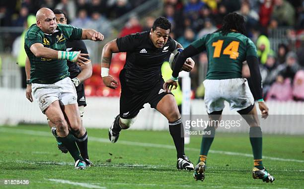Sione Lauaki of the All Blacks runs the ball at Odwana Ndungane as Gurthro Steenkamp backs up during the 2008 Tri Nations series match between the...
