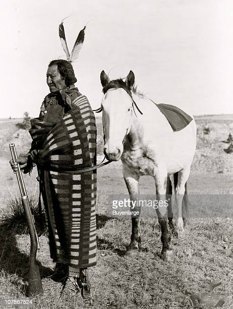 Sioux Indian fulllength portrait facing left holding rifle in front of horse 1900