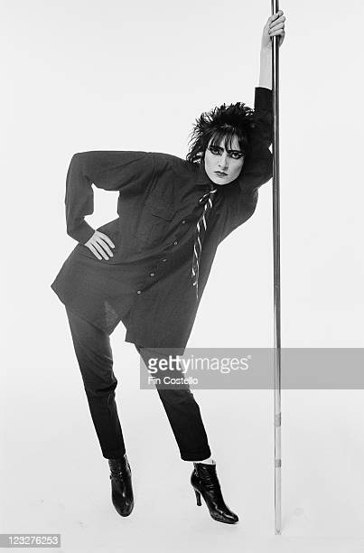 Siouxsie Sioux singer with British punk band Siouxsie and the Banshees poses holding onto a veritical stainless steel pole in a studio portrait...