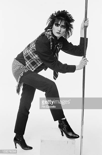 Siouxsie Sioux singer with British punk band Siouxsie and the Banshees poses holding onto a vertical stainless steel pole in a studio portrait...
