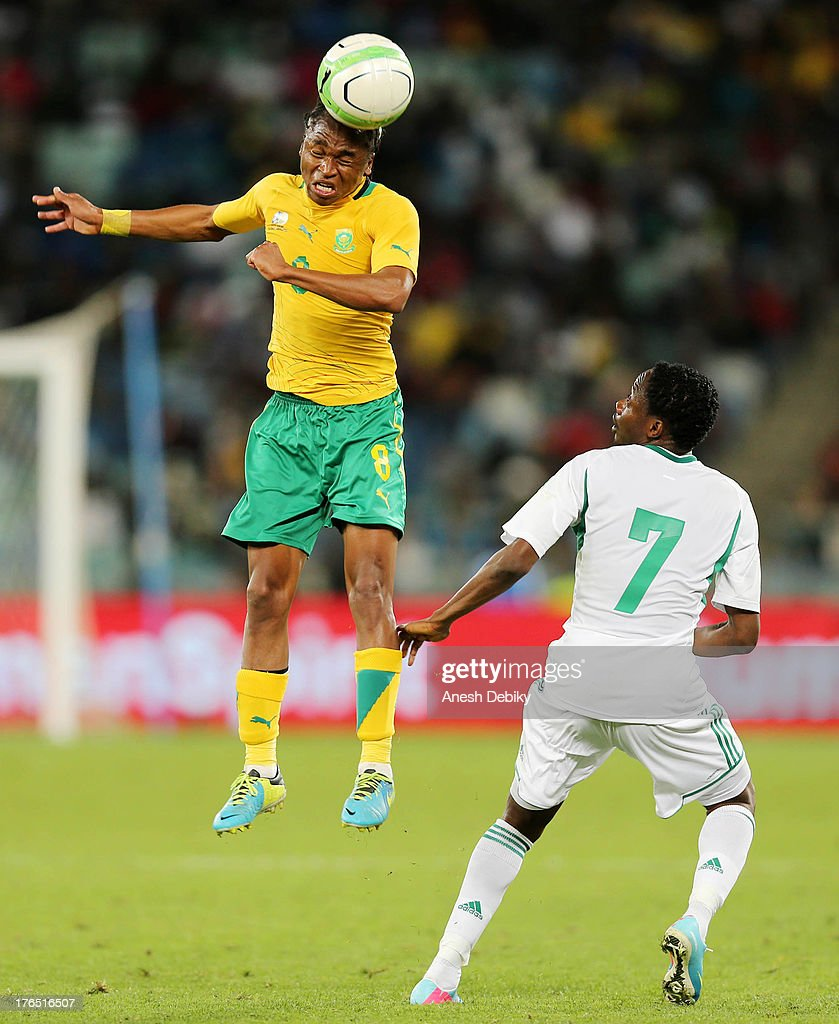 Siphiwe Tshabala of South Africa (L) heads the ball past Ahmed Musa of Nigeria during the 2013 Nelson Mandela Challenge match between South Africa and Nigeria at Moses Mabhida Stadium on August 14, 2013 in Durban, South Africa.