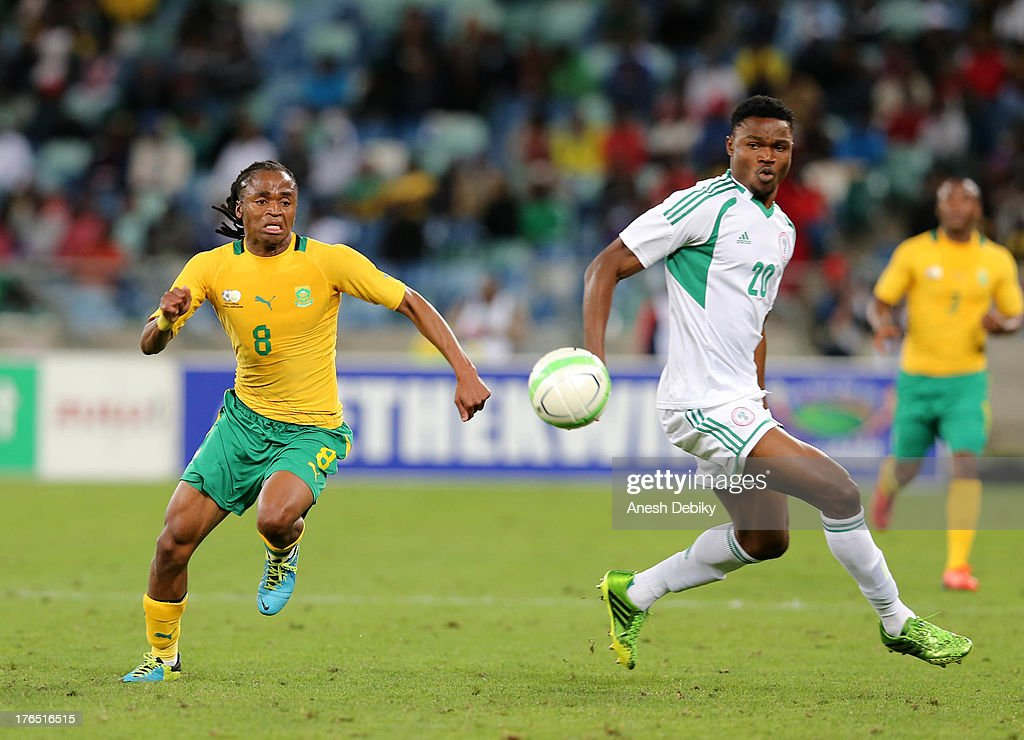 Siphiwe Tshabalala of South Africa (L) and James Okwuosa of Nigeria lose the ball during the 2013 Nelson Mandela Challenge match between South Africa and Nigeria at Moses Mabhida Stadium on August 14, 2013 in Durban, South Africa.