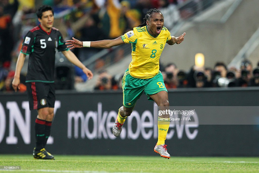 <a gi-track='captionPersonalityLinkClicked' href=/galleries/search?phrase=Siphiwe+Tshabalala&family=editorial&specificpeople=788347 ng-click='$event.stopPropagation()'>Siphiwe Tshabalala</a> of South Africa celebrates after scoring the opening goal while <a gi-track='captionPersonalityLinkClicked' href=/galleries/search?phrase=Ricardo+Osorio&family=editorial&specificpeople=224529 ng-click='$event.stopPropagation()'>Ricardo Osorio</a> of Mexico looks dejected during the 2010 FIFA World Cup South Africa Group A match between South Africa and Mexico at Soccer City Stadium on June 11, 2010 in Johannesburg, South Africa.