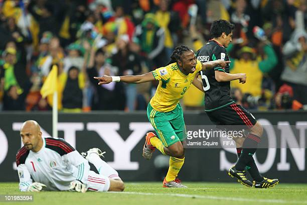 Siphiwe Tshabalala of South Africa celebrates after scoring the opening goal while Ricardo Osorio and goalkeeper Oscar Perez of Mexico look dejected...