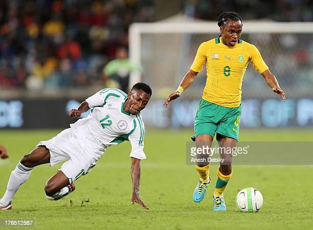 Siphiwe Tshabalala of South Africa goes around Nnamadi Oduamadi of Nigeria during the 2013 Nelson Mandela Challenge match between South Africa and...