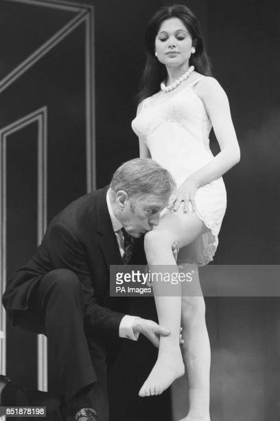 Sir Alec Guinness kisses the knee of Madeline Smith during a rehearsal of Alan Bennett's Habeas Corpus at the Lyric Theatre