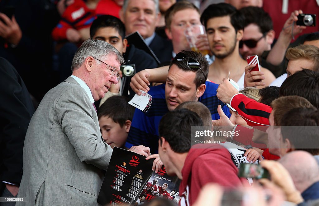 Sir <a gi-track='captionPersonalityLinkClicked' href=/galleries/search?phrase=Alex+Ferguson&family=editorial&specificpeople=203067 ng-click='$event.stopPropagation()'>Alex Ferguson</a>, formerly of Manchester United signs autographs during the charity match between Manchester United Legends and Real Madrid Legends at Old Trafford on June 2, 2013 in Manchester, England.