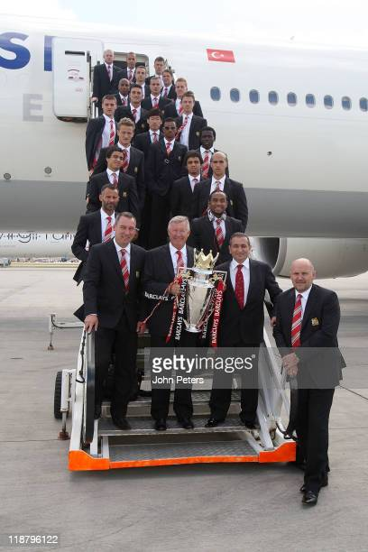 Sir Alex Ferguson of Manchester United poses with the Premier League trophy and the Manchester United squad at Manchester Airport ahead of their...