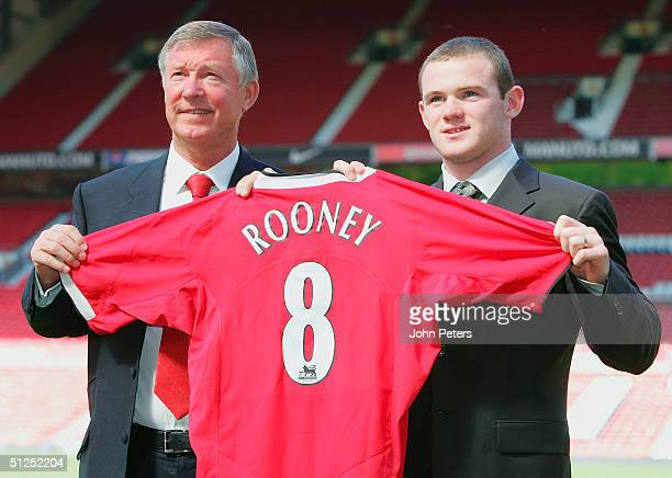 Sir Alex Ferguson of Manchester United poses with Wayne Rooney and a United shirt after a press conference to unveil Manchester United's new signing...