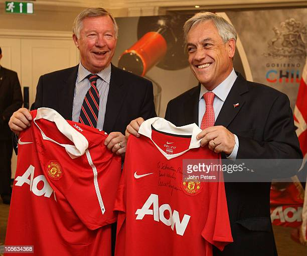 Sir Alex Ferguson of Manchester United presents Chilean president Sebastian Pinera with a signed Manchester United shirt as a gift to the 33 miners...