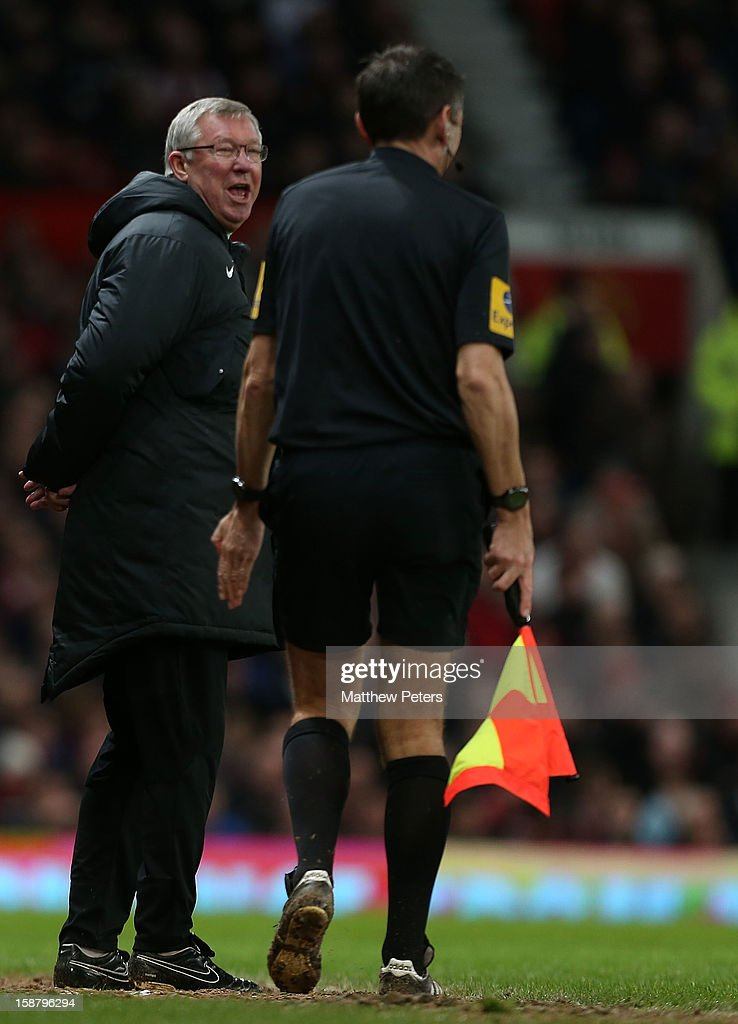 Sir Alex Ferguson of Manchester United shares a joke with assistant referee Andy Garratt during the Barclays Premier League match between Manchester United and West Bromwich Albion at Old Trafford on December 29, 2012 in Manchester, England.