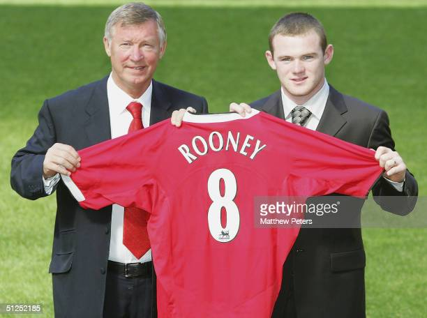 Sir Alex Ferguson poses with Wayne Rooney of Mancester United and a Manchester United shirt after the press conference to unveil Manchester United's...