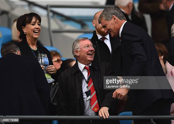 Sir Alex Ferguson smiles at David Gill former chief executive of Manchester United during the Barclays Premier League match between Manchester City...
