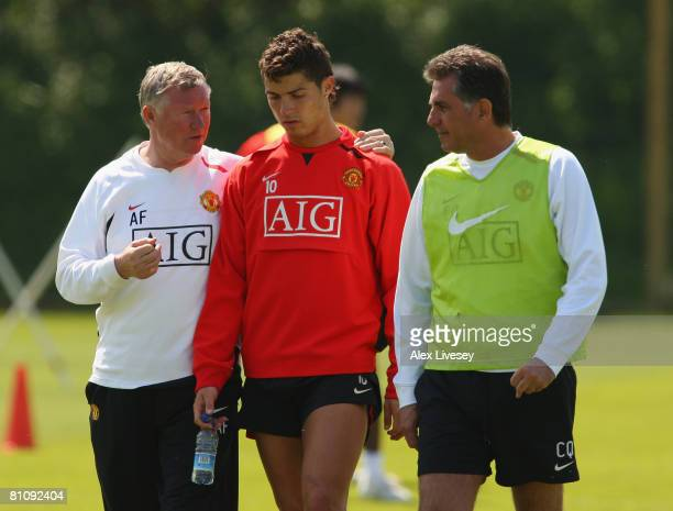 Sir Alex Ferguson the manager of Manchester United and his assistant Carlos Queiroz talk with Cristiano Ronaldo ahead of the UEFA Champions League...