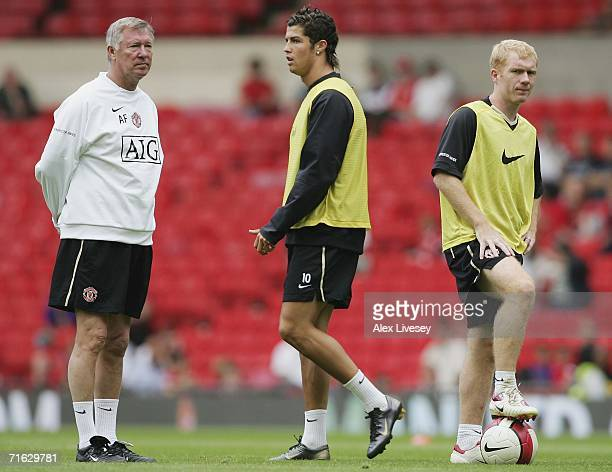 Sir Alex Ferguson the manager of Manchester United watches as Cristiano Ronaldo and Paul Scholes train during a Manchester United training session...