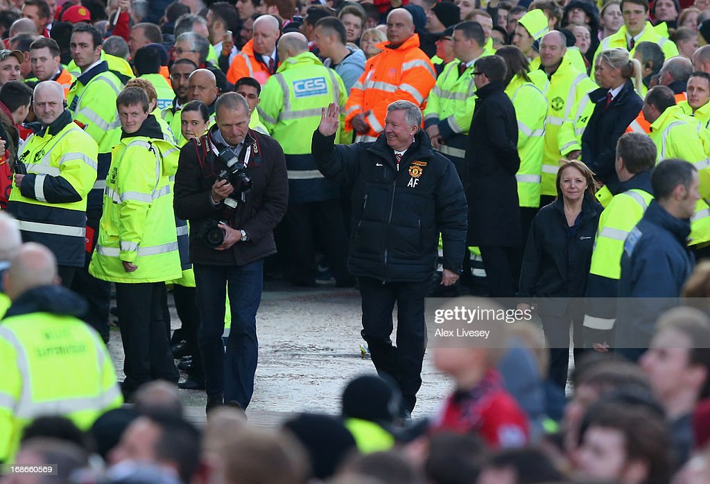 Sir Alex Ferguson waves to fans as he arrives for the Manchester United Premier League winners parade on May 13, 2013 in Manchester, England.