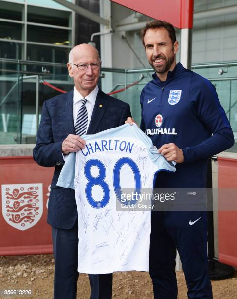 Sir Bobby Charlton is presented with a signed shirt by Gareth Southgate manager of England as a pitch is named in his honour during an England...