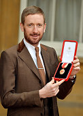 Sir Bradley Wiggins CBE holds his Knighthood award after it was presented to him by Queen Elizabeth II at an Investiture ceremony at Buckingham...