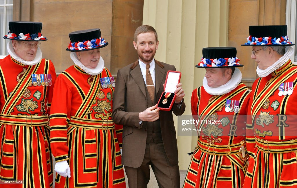 Sir Bradley Wiggins CBE holds his Knighthood award as he is surrounded by Yeomen of the Guard after it was presented to him by Queen Elizabeth II at...