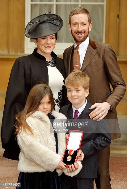Sir Bradley Wiggins CBE poses with his wife Catherine and children Isabella and Ben after he was awarded a Knighthood by Queen Elizabeth II at an...
