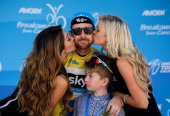 Sir Bradley Wiggins of Great Britain riding for Team Sky is kissed by the flower girls while his son Ben looks on following stage eight of the 2014...