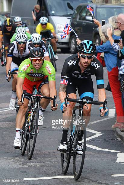 Sir Bradley Wiggins rides in the peloton ahead of Sebastian Lander of Denmark and BMC Racing Team as it passes through Bradford on Avon during Stage...