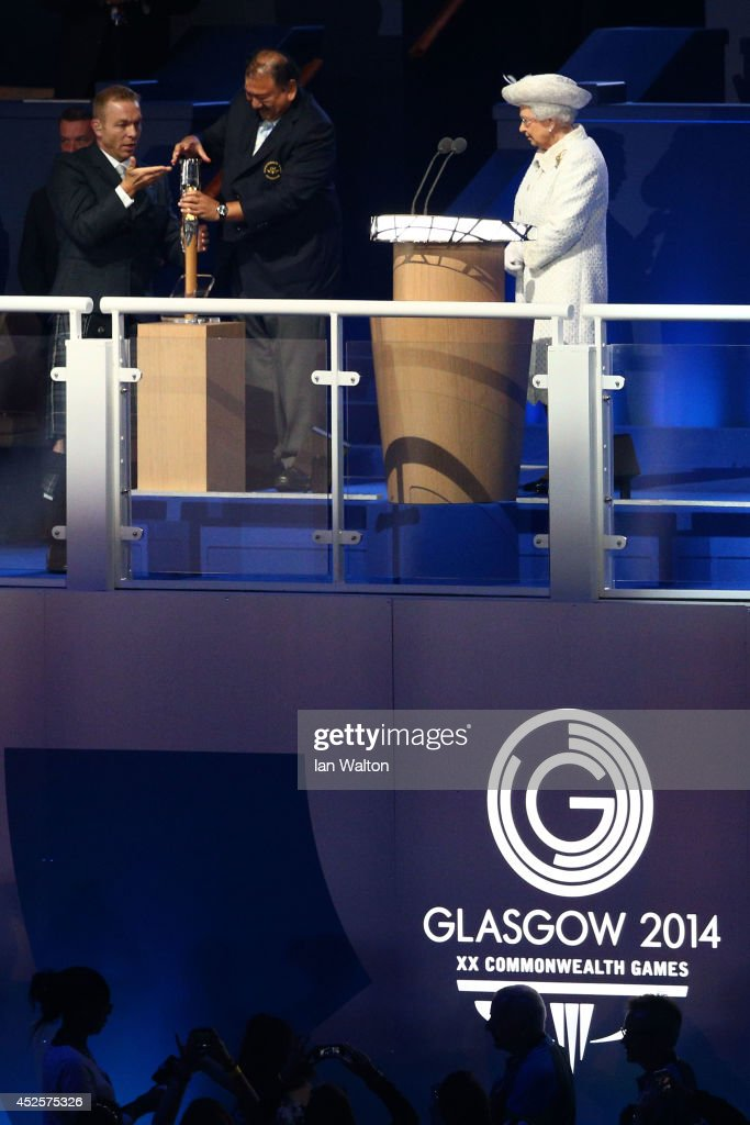 Sir Chris Hoy assists Prince Imran the CGF President attempts to retrieve the message from the baton as he presents it to Queen Elizabeth II, Patron of the CGF during the Opening Ceremony for the Glasgow 2014 Commonwealth Games at Celtic Park on July 23, 2014 in Glasgow, Scotland.