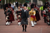 Sir Chris Hoy MBE walks up The Mall holding the Queen's Baton with The Pipes and Drums The Scotts Guards at Buckingham Palace on October 9 2013 in...