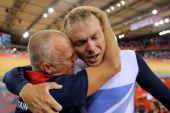 Sir Chris Hoy of Great Britain celebrates with coach Shane Sutton after setting a new world record and winning gold in the Men's Team Sprint Track...