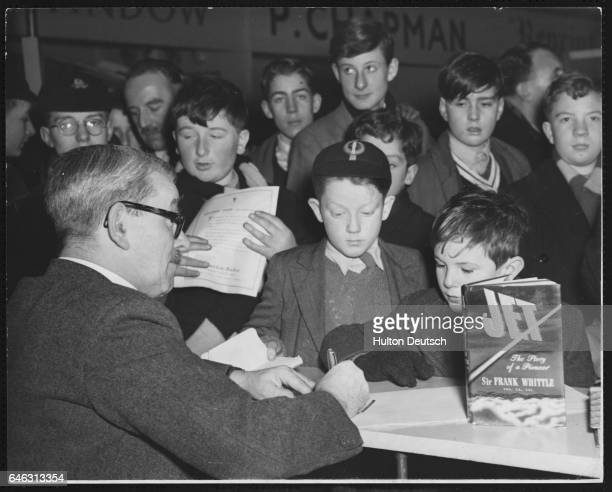 Sir Frank Whittle the English aeronautical engineer and inventor of the jet engine signs copies of his book Jet for waiting schoolboys at an...