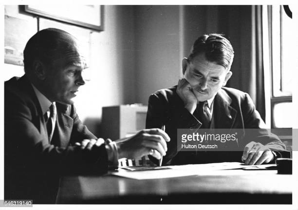 Sir Frank Whittle the English aeronautical engineer and inventor of the jet engine sits studying documents with another man