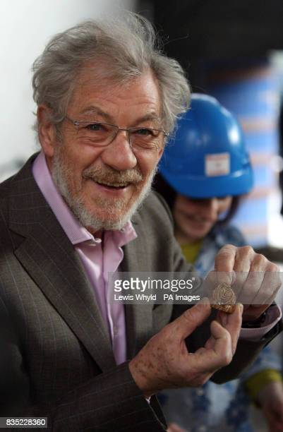 Sir Ian McKellen holds a piece of 16th century pottery found during a visit to the site of Shakespeare's first playhouse which has been uncovered by...