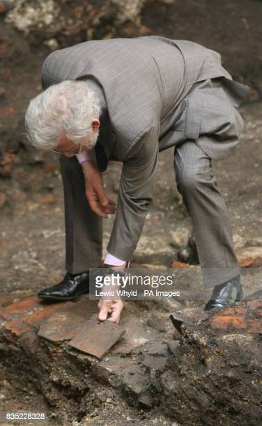 Sir Ian McKellen inspects a piece of flooring during a visit to the site of Shakespeare's first playhouse which has been uncovered by Museum of...