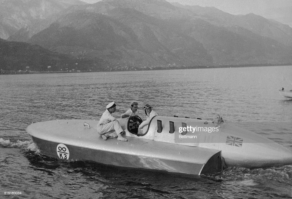 Sir Malcolm Campbell in cockpit and his mechanics as they tuned up the Bluebird for an attempt to set a record on the waters of Lake Locarno...