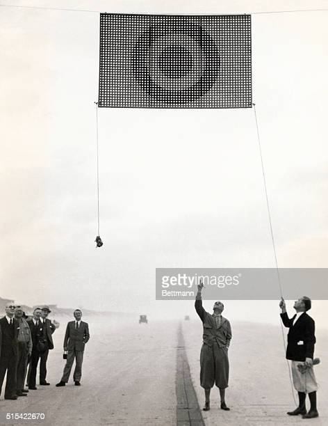 Sir Malcolm Campbell who will try to beat his own record of 272108 mph speed over the measured mile beach course here inspecting the suspended...