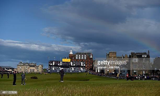 Sir Nick Faldo of England celebrates his putt for birdie on the 17th green as a rainbow is seen in the distance during the second round of the 144th...