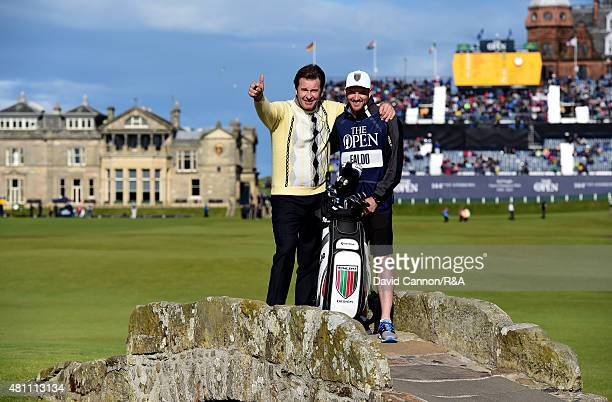 Sir Nick Faldo of England waves to the crowd as he stands on Swilcan Bridge with his son and caddie Matthew Faldo during the second round of the...
