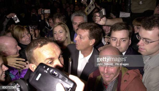 Sir Paul McCartney and his fiancee Heather Mills fight their way through enthusiastic fans as they make thier way to the stage door of the Queens...