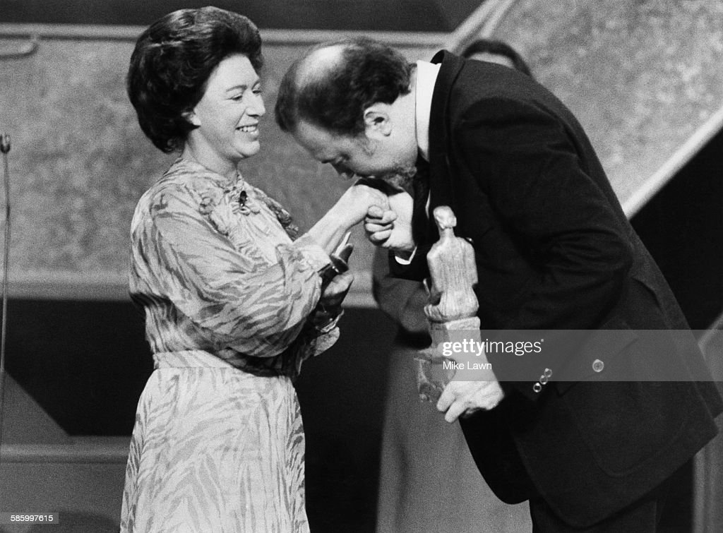 Sir Peter Hall, director of the National Theatre, kisses the hand of Princess Margaret (1930 - 2002) after she presented him with a special award marking his 25 years as a director, at the Evening Standard Drama Awards, held at the National Theatre, London, 29th January 1980.