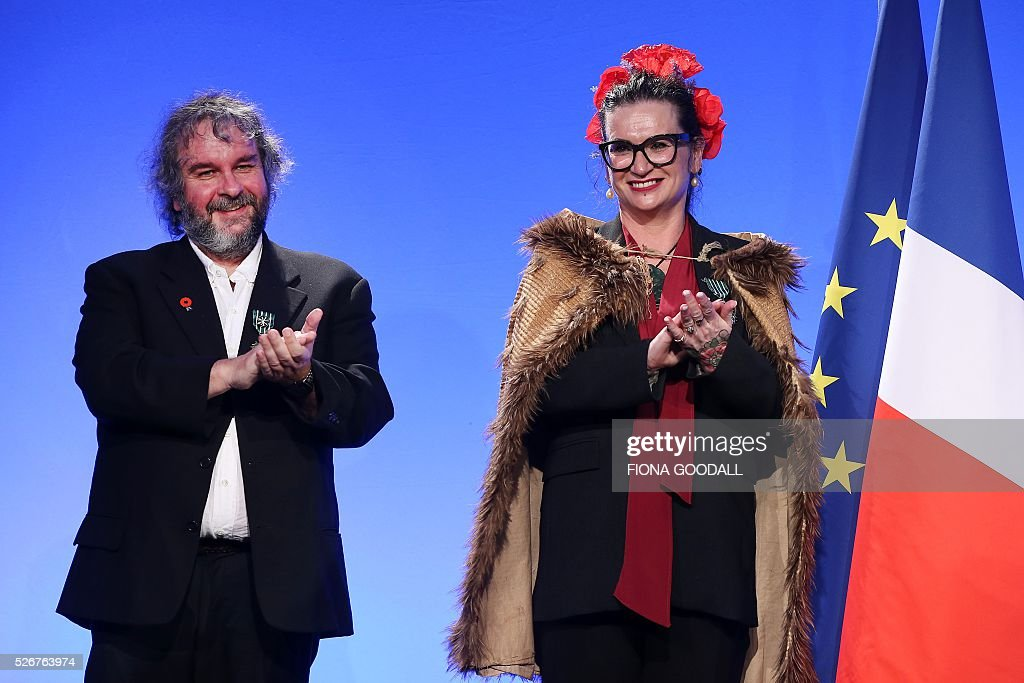 Sir Peter Jackson (L) and Fiona Pardington (R) listen as French Prime Minister Manuel Valls presents them with a Ordre des Arts et des Lettres medal at a French community event at Auckland War Memorial Museum on May 1, 2016. / AFP / Fiona Goodall