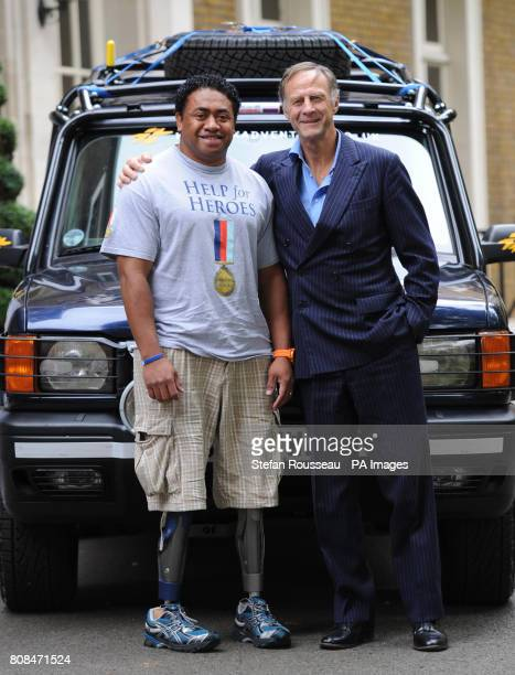 Sir Ranulph Fiennes with double amputee Private Derek Derenalagi pose in front of a Land Rover Discovery 2 at the Society of Motor Manufacturers and...