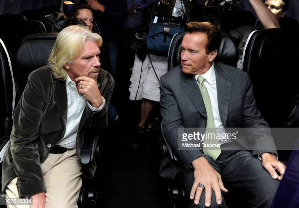 Sir Richard Branson and California Governor Arnold Schwarzenegger sit in the main cabin of Virgin America's first international flight to Toronto on...